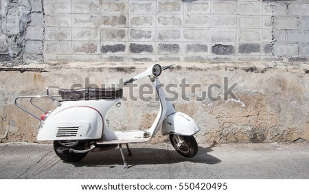 white  scooter stands parked near the concrete old wall,white scooter stands parked near the concrete old wall with blue sky background,white Classic Motorcycles #550420495