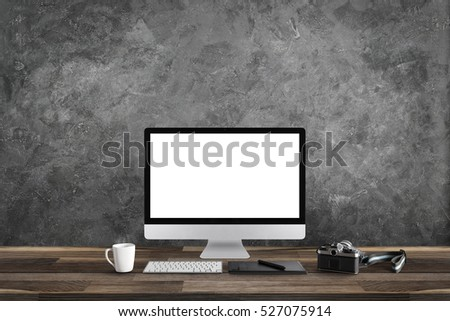 White screen computer in room on gray table and camera film, workplace with cement wall #527075914