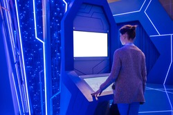 White screen, mock up, future, copyspace, technology concept. Woman looking at blank interactive touchscreen white display of electronic kiosk at exhibition or museum with sci-fi blue interior