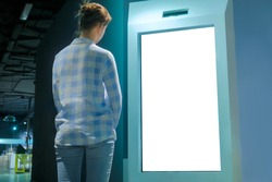 White screen, mock up, future, copyspace, template, isolated, technology concept. Woman looking at blank interactive touchscreen white display of electronic kiosk at futuristic exhibition or museum