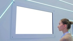 White screen, mock up, future, copyspace, template, isolated, technology concept. Woman looking at blank digital interactive white display wall at exhibition or museum with futuristic scifi interior