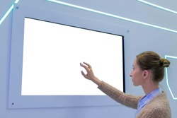 White screen, mock up, future, copyspace, template, isolated, technology concept. Woman touching blank digital interactive white display wall at exhibition or museum with futuristic scifi interior