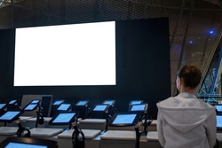 White screen, scifi, technology, futuristic, template, mock up, entertainment concept. Woman looking at large wall blank interactive white display at science exhibition, museum or cinema