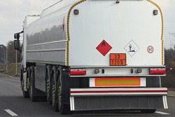 White semi truck fuel tanker with 33/1203 dangerous class sign and copy space place blank on barrel drive on asphalt highway on a spring day on blue sky background, side rear view ADR hazardous cargo