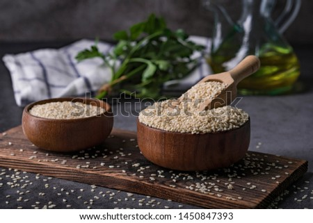 White sesame seeds in a wooden spoon on dark table, Sesame oil in jar and seeds concept, Sesame dark tone background. Stockfoto ©