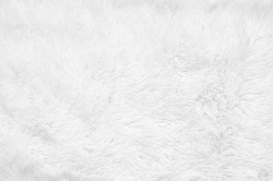 White shaggy blanket texture as background. Fluffy fake textile fur.