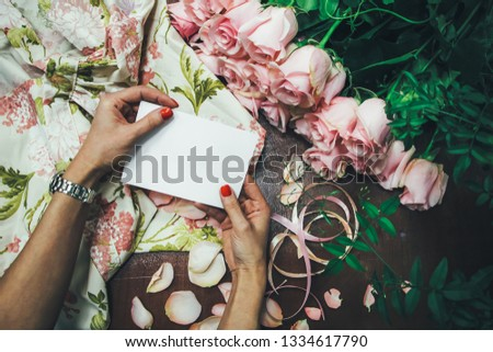 White sheet in hands on a wooden background, next to flowers and colorful ribbons. A clean greeting card. Layout for artists. Layout for artists. Mockup. #1334617790
