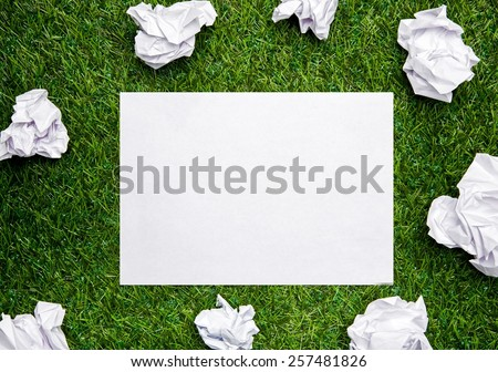 White sheet of paper with cramled sheets on the grass