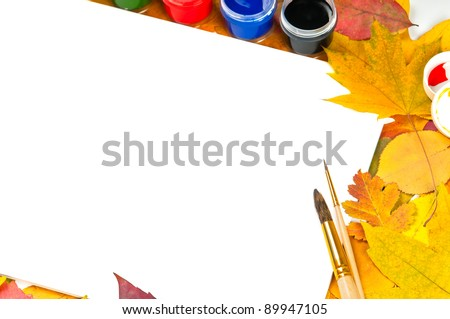 white sheet of paper with paints and brushes on the background of autumn leaves