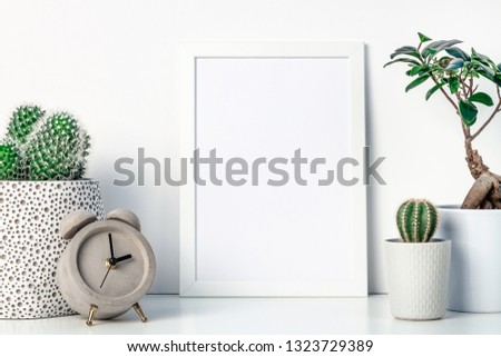 White shelf at home. Cactus and bonsai decoration in concrete and ceramic pots. Concrete clock. White empty frame mockup. Space for text or graphics