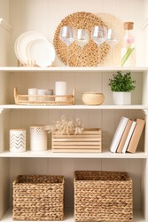 White shelving unit with dishware and different decorative stuff