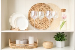 White shelving unit with glasses and different decorative stuff