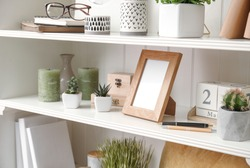 White shelving unit with plants and different decorative stuff