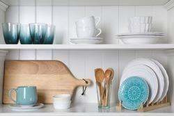 White shelving unit with set of dishware
