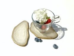 White shimmer Pearl coasters of epoxy resin with a golden edge, ripe red strawberries, blueberries and white hydrangea in a transparent glass cup