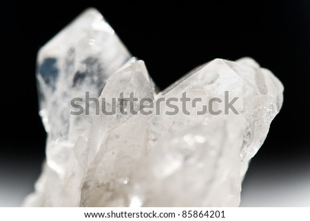 white shining rock mountain crystall quarz on black ground - stock photo