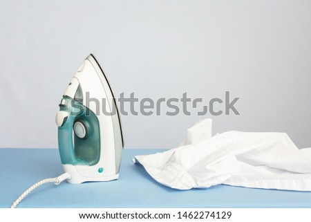 White shirt and iron, blue ironing board, closeup, side view, copy pace, toned. Concept housework