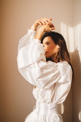 White shirt featuring long puff sleeves with cuffs and a button-up front and leather white corset in trendy minimalistic style. Light from sun on the face and shadow from hands. Woman hiding from sun.