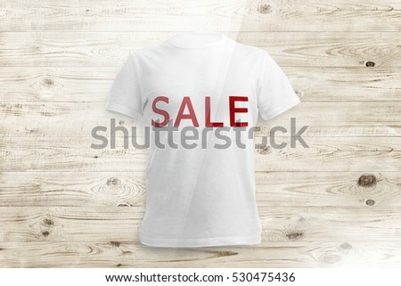 White shirt with inscription SALE over wood background #530475436
