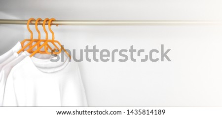 White shirts hanging on rack in wardrobe closet. Female different clothes in on yellow hangs