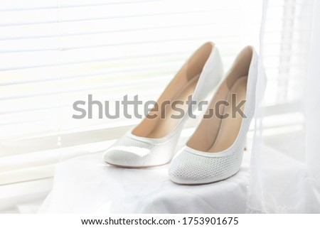 white shoes for the bride stand on the windowsill against the background of the blinds