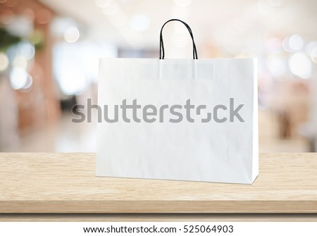 White shopping bag on wooden table over blurred store background, business, template, retail, sale, product display montage