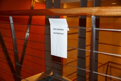 white sickness bag hangs on a stair railing of a cruise ship, barf bag