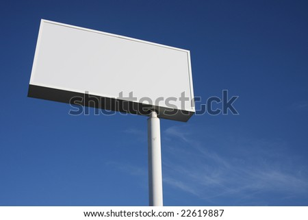 White sign against a blue sky - stock photo