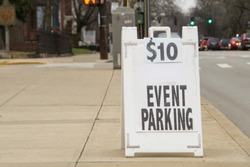 White Sign that says $10 Event Parking on sidewalk