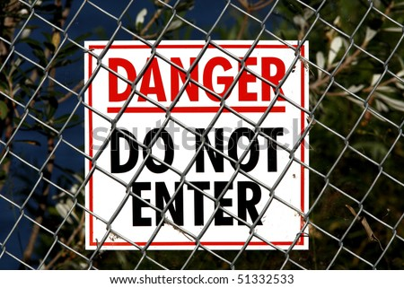 White sign with Red and Black writing saying Danger Do Not Enter and attached to a wire fence. There are spiders webs and plant material on the fence and sign