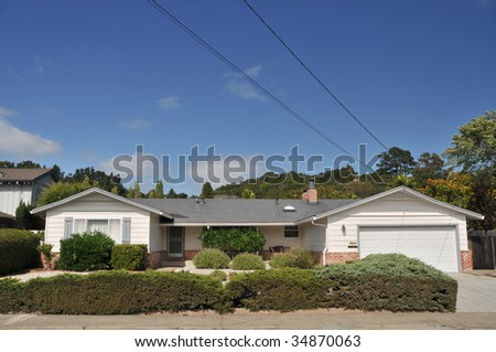 White single family house with grass in front has wires and cables coming off the roof