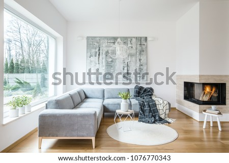 White sitting room interior with grey corner sofa, tulips in vase placed on an end table, fireplace and modern art painting