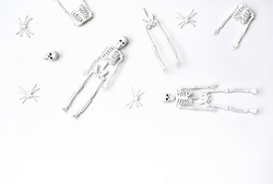 White skeletons and spiders on the white background. Minimalism style flat lay. Concept of Halloween or Day of the dead.