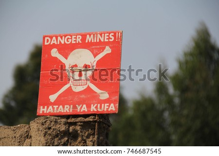 White skull-and-crossbones symbol on a red sign warning of the danger of landmines, Democratic Republic of Congo Stock photo ©