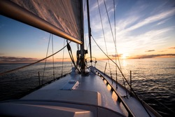 White sloop rigged yacht sailing at sunset.A view of the deck, bow, mast and sails. Baltic sea, Latvia. Transportation, nautical vessel, cruise, sport, regatta, recreation, leisure activity