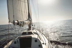 White sloop rigged yacht sailing in an open sea at sunset. Clear sky. A view from the deck to the bow, mast, sails. Transportation, travel, cruise, sport, recreation, leisure activity, racing, regatta