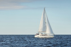 White sloop rigged yacht sailing in the Baltic sea at sunset. Clear sky after the storm, soft sunlight. Transportation, travel, cruise, sport, recreation, leisure activity, racing, regatta