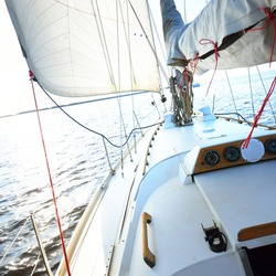 White sloop rigged yacht sailing in the Baltic sea. Clear blue sky. A view from the deck to the bow, mast, sails. Transportation, travel, cruise, sport, recreation, leisure activity, racing, regatta