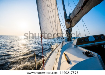 White sloop rigged yacht sailing on a clear day. Close-up of the deck, bow, mast, sails. Brittany, France. Transportation, sport, recreation, leisure activity, regatta, travel, vacations, adventure