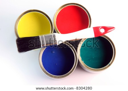 white small paint brush on four open paint cans on white background