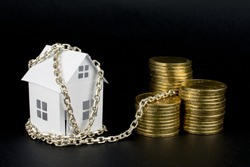 white small paper house tied with chain to the money golden coins, loan money secured by immovable property concept, close up, selective focus , blurred dark background