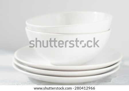 white small plates and bowls on a light table