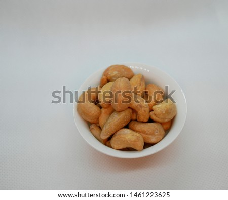 white small porcelain bowl filled with cashew nuts. Natural vitamin. Healthy food. vegetarian food.