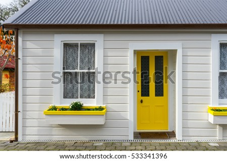 White small wooden house with yellow door