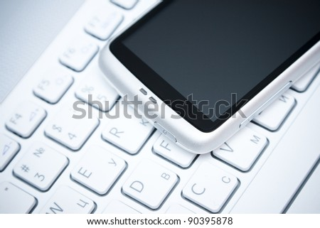 white smart phone on laptop keyboard background - stock photo