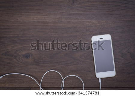White smart phone with headphones cable on the wooden table