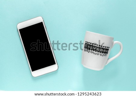 white smartphone iphone with black screen and cup with title espresso on blue paper background #1295243623