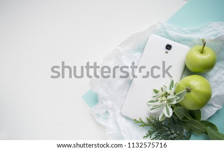 white smartphone lies on the table. Green apples next to the phone. business woomen Mockup for copyspace tender in turquoise-green tones with a white background.