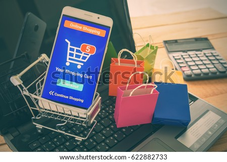 White smartphone runs an online shopping app put in a shopping cart on a laptop keyboard. Online shopping is the purchase of products and services on the internet that has become increasingly popular. #622882733