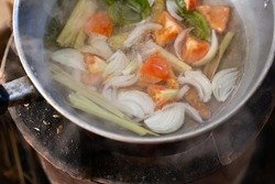 White smoke from cooking and tomato, onion, Lemongrass in stainless pot on stove in countryside kitchen. Thai food. Soft picture